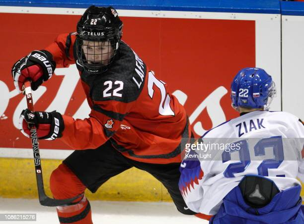 Alexis Lafreniere of Team Canada skates around Adam Ziak of Team Slovakia at the IIHF World Junior Championships at the SaveonFoods Memorial Centre...