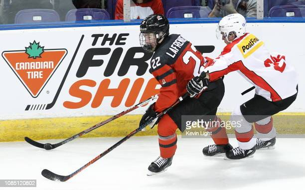 Alexis Lafreniere of Team Canada skates with the puck while being chased by David Aebischer of Team Switzerland at the IIHF World Junior...