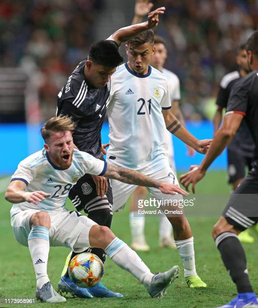 Alexis Mac Allister of Argentina Jesus Gallardo of Mexico and Paulo Dybala of Argentina struggle for control of the ball during the International...