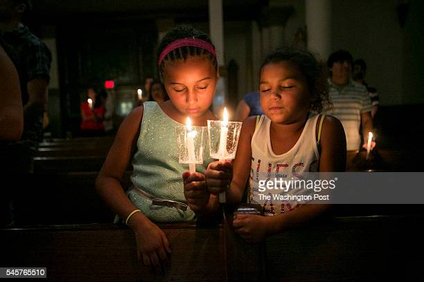 Alexis McCormick and Michaela McCormick hold candles to honor those killed in Dallas yesterday Mourners pray and light a candel in honor of those...