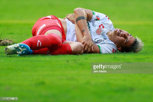 Alexis Pena of Necaxa lies on the grass after being injured during the 9th round match between Monterrey and Necaxa as part of the Torneo Apertura...
