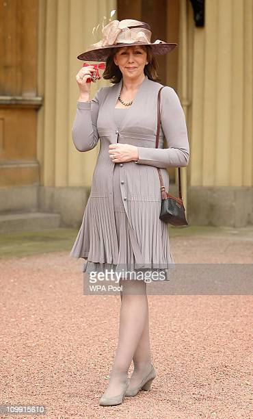 Alexis Redmond holds her MBE medal presented by Britain's Queen Elizabeth II during an investiture ceremony at Buckingham Palace on March 10 2011 in...
