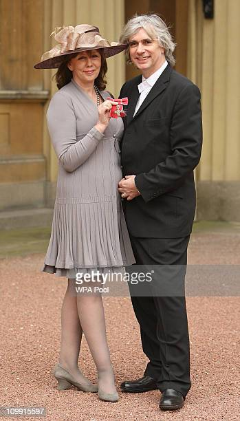 Alexis Redmond with her husband Phil Redmond holds her MBE medal presented by Britain's Queen Elizabeth II during an investiture ceremony at...
