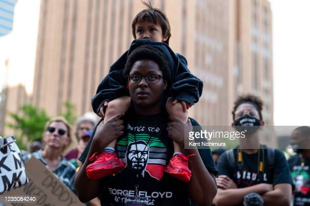 Alexis Rodgers of Minneapolis, with Caden the child of a friend, on her shoulders, during the inaugural remembrance rally and march hosted by the...