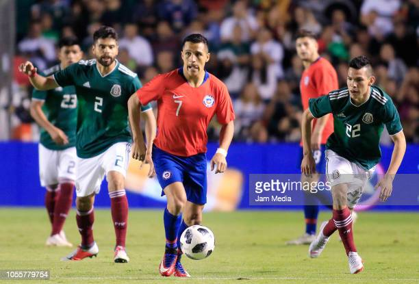 Alexis Sanches of Chile fights for the ball with Hirving Lozano of Mexico during the international friendly match between Mexico and Chile at La...