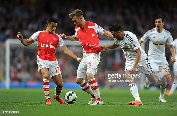 Alexis Sanchez and Aaron Ramsey of Arsenal challenged by Neil Taylor of Swansea during the Barclays Premier League match between Arsenal and Swansea...