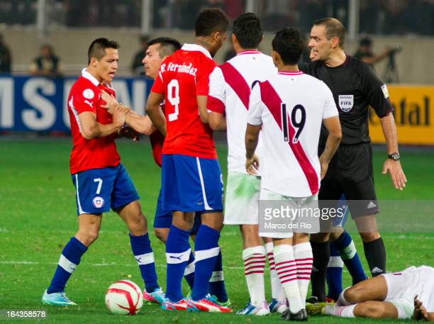 Alexis Sanchez and Junior Fernandez of Chile and Victor Yotun of Peru discuss with the referee during a match between Peru and Chile as part of the...