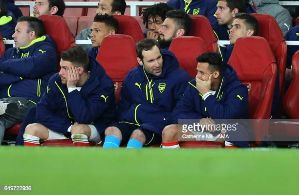 Alexis Sanchez appears to smirk as he Aaron Ramsey and Petr Cech of Arsenal watch from the bench during the UEFA Champions League Round of 16 second...