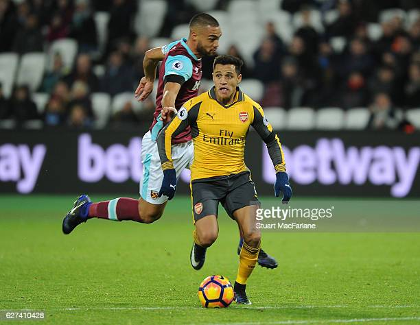 Alexis Sanchez breaks past West Ham defender Winston Reid to score the 5th Arsenal goal during the Premier League match between West Ham United and...