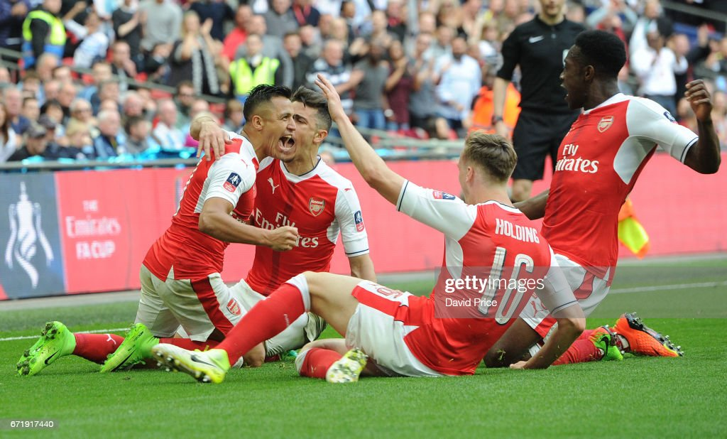 Alexis Sanchez celebrates scoring Arsenal's 2nd goal with Rob Holding and Danny Welbeck during the match between Arsenal and Manchester City at Wembley Stadium on April 23, 2017 in London, England.