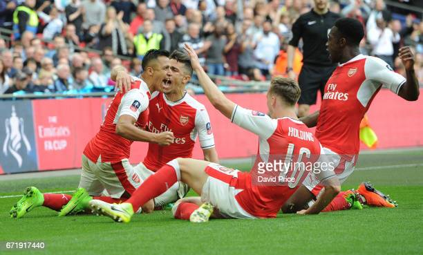 Alexis Sanchez celebrates scoring Arsenal's 2nd goal with Rob Holding and Danny Welbeck during the match between Arsenal and Manchester City at...