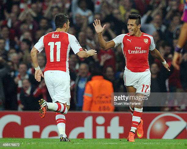 Alexis Sanchez celebrates scoring the 3rd Arsenal goal with Mesut Ozil during the Champions League match between Arsenal and Galatasaray at Emirates...