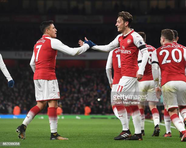 Alexis Sanchez celebrates scoring the 3rd Arsenal goal with Mesut Ozil during the Premier League match between Arsenal and Huddersfield Town at...