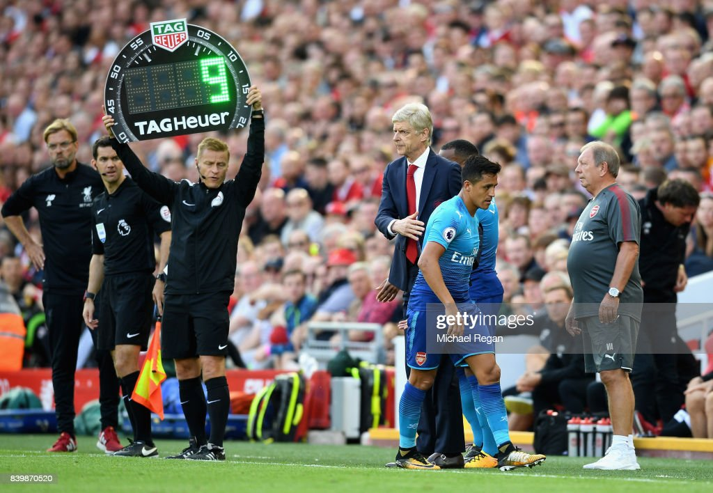 Alexis Sanchez of Arsenal and Arsene Wenger, Manager of Arsenal embrace after he is subbed during the Premier League match between Liverpool and Arsenal at Anfield on August 27, 2017 in Liverpool, England.