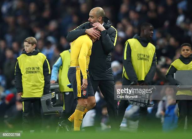 Alexis Sanchez of Arsenal and Josep Guardiola Manager of Manchester City embrace after the final whistle during the Premier League match between...