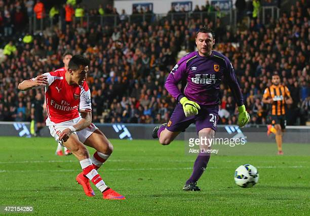 Alexis Sanchez of Arsenal beats goalkeeper Steve Harper of Hull City as he scores their third goal during the Barclays Premier League match between...