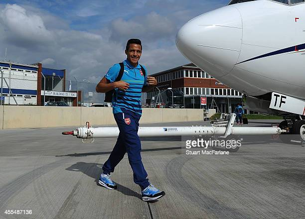 Alexis Sanchez of Arsenal boards the team plane at Luton Airport on September 15 2014 in St Albans England Photo by Stuart MacFarlane/Arsenal FC via...