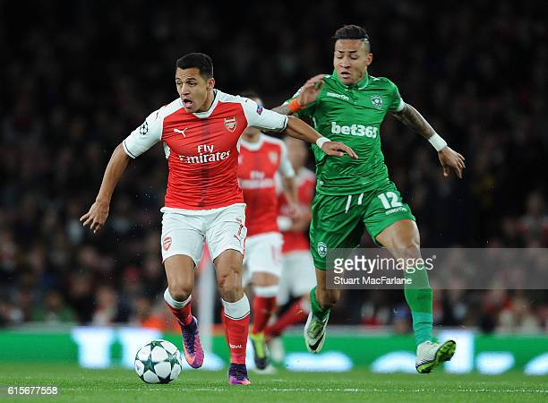 Alexis Sanchez of Arsenal breaks past Anicet Abel of Ludogorets during the UEFA Champions League match between Arsenal FC and PFC Ludogorets Razgrad...