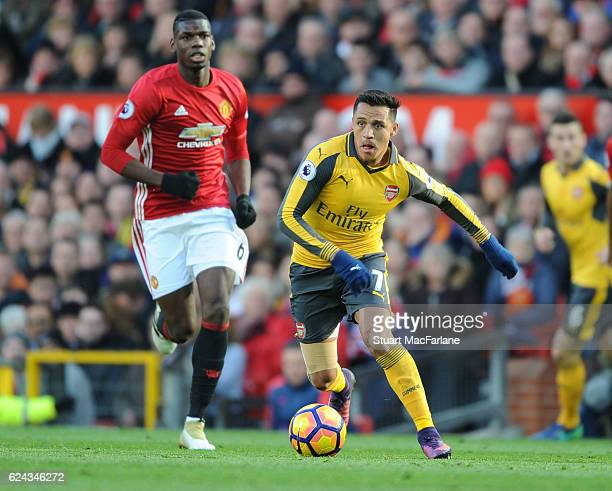 Alexis Sanchez of Arsenal breaks past Paul Pogba of Man United during the Premier League match between Manchester United and Arsenal at Old Trafford...