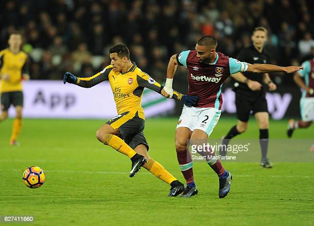 Alexis Sanchez of Arsenal breaks past Winston Reid of West Ham during the Premier League match between West Ham United and Arsenal at London Stadium...