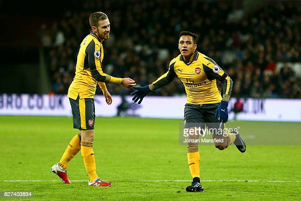 Alexis Sanchez of Arsenal celebrates after scoring his team's third goal with Aaron Ramsey during the Premier League match between West Ham United...