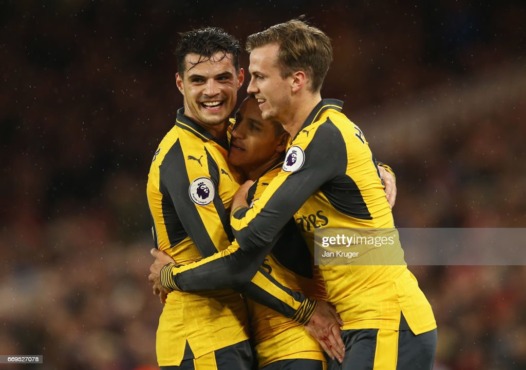 Alexis Sanchez of Arsenal (7) celebrates as he scores their first goal with Granit Xhaka (L) and Rob Holding (R) during the Premier League match between Middlesbrough and Arsenal at Riverside Stadium on April 17, 2017 in Middlesbrough, England.