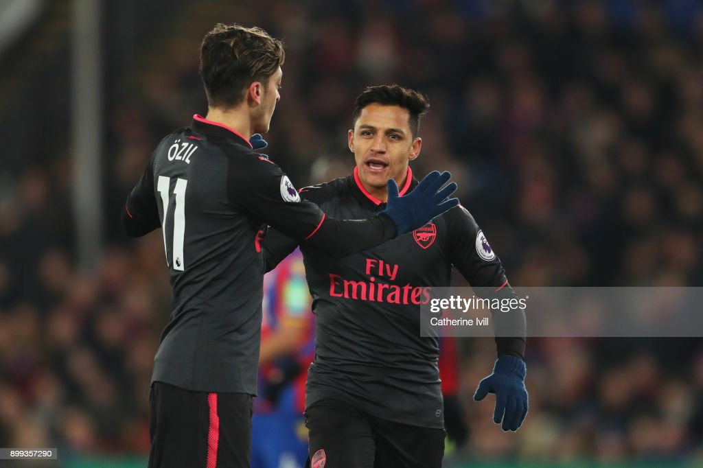 Alexis Sanchez of Arsenal celebrates as he scores their second goal with Mesut Ozil during the Premier League match between Crystal Palace and Arsenal at Selhurst Park on December 28, 2017 in London, England.