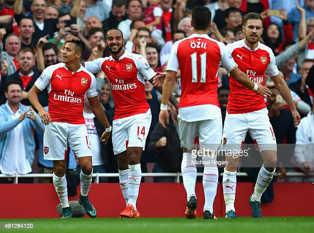 Alexis Sanchez of Arsenal celebrates scoring their third goal with team mates during the Barclays Premier League match between Arsenal and Manchester...
