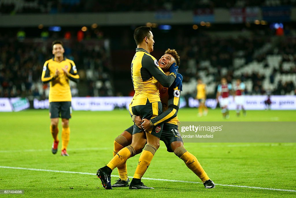 Alexis Sanchez of Arsenal celebrates with Alex Oxlade-Chamberlain after scoring his team's fifth goal and completes his hat trick during the Premier League match between West Ham United and Arsenal at London Stadium on December 3, 2016 in London, England.