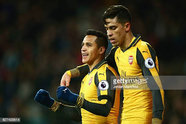 Alexis Sanchez of Arsenal celebrates with Gabriel Paulista after scoring his team's second goal during the Premier League match between West Ham...