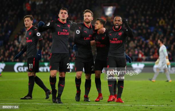Alexis Sanchez of Arsenal celebrates with Granit XhakaShkodran Mustafi and Alexandre Lacazette of Arsenal during the Premier League match between...