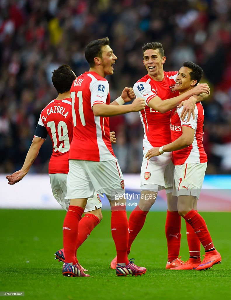 Alexis Sanchez of Arsenal (R) celebrates with Santi Cazorla (L), Mesut Oezil (2L) and Gabriel (2R) as he scores their second goal during the FA Cup Semi Final between Arsenal and Reading at Wembley Stadium on April 18, 2015 in London, England.