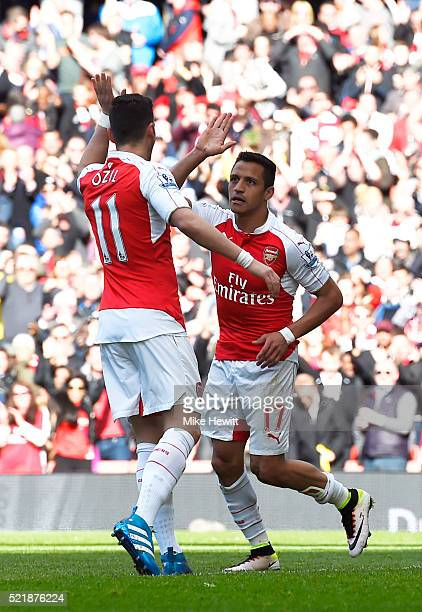 Alexis Sanchez of Arsenal celebrates with team mate Mesut Ozil of Arsenal after scoring the opening goal of the game during the Barclays Premier...