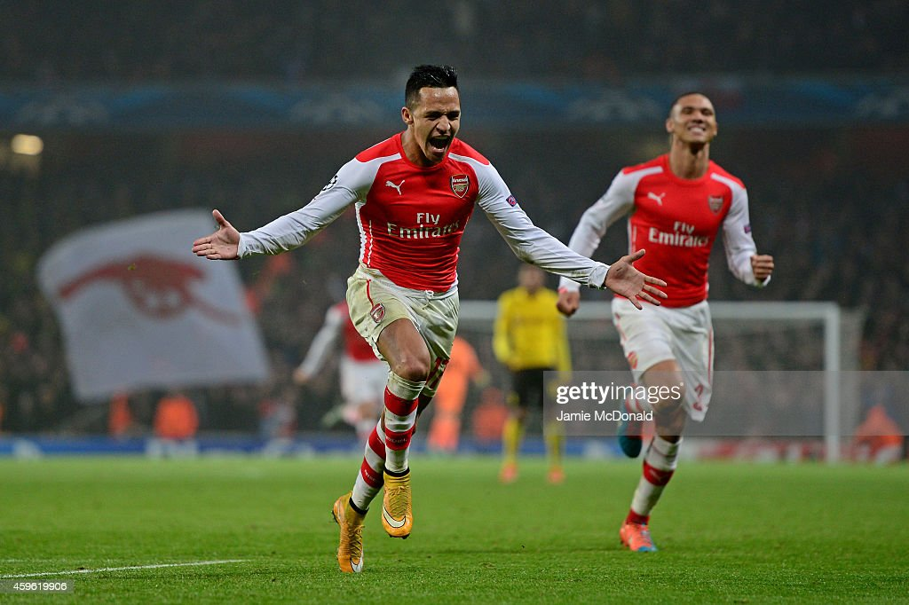 Alexis Sanchez of Arsenal celebrates with teammate Kieran Gibbs (R) after scoring his team's second goal during the UEFA Champions League Group D match between Arsenal and Borussia Dortmund at the Emirates Stadium on November 26, 2014 in London, United Kingdom.