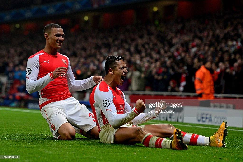 Alexis Sanchez of Arsenal celebrates with teammate Kieran Gibbs (L) after scoring his team's second goal during the UEFA Champions League Group D match between Arsenal and Borussia Dortmund at the Emirates Stadium on November 26, 2014 in London, United Kingdom.