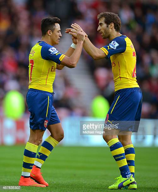 Alexis Sanchez of Arsenal celebrates with teammate Mathieu Flamini after scoring the opening goal during the Barclays Premier League match between...