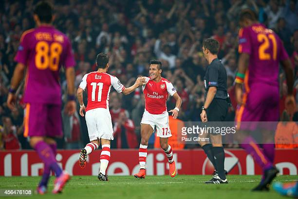 Alexis Sanchez of Arsenal celebrates with teammate Mesut Oezil after scoring his team's third goal during the UEFA Champions League group D match...