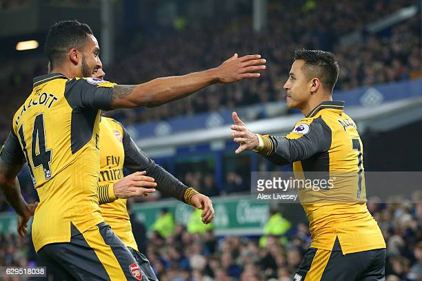 Alexis Sanchez of Arsenal celebrates with teammate Theo Walcott after scoring the opening goal during the Premier League match between Everton and...