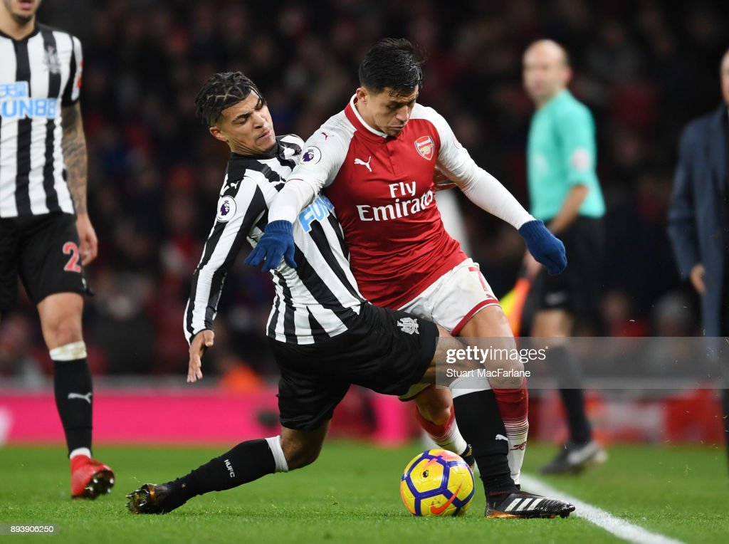 Alexis Sanchez of Arsenal challengd by DeAndre Yedlin of Newcastle during the Premier League match between Arsenal and Newcastle United at Emirates Stadium on December 16, 2017 in London, England.