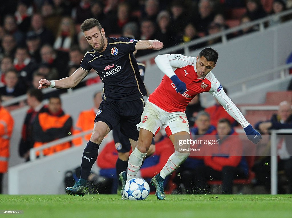 Alexis Sanchez of Arsenal challenged by Ivo Pinto of Zagreb during the match between Arsenal and Dinamo Zagreb in the UEFA Champions League on November 24, 2015 in London, United Kingdom.