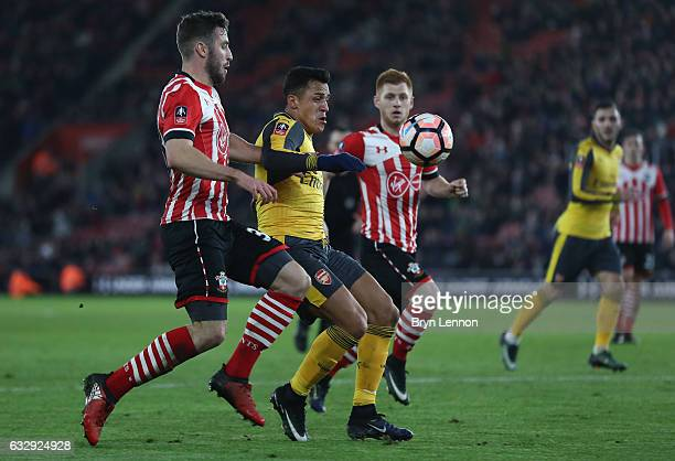 Alexis Sanchez of Arsenal challenges for the ball with Sam McQueen of Southampton during the Emirates FA Cup Fourth Round match between Southampton...