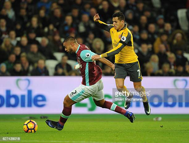 Alexis Sanchez of Arsenal challenges Winston Reid of West Ham during the Premier League match between West Ham United and Arsenal at London Stadium...