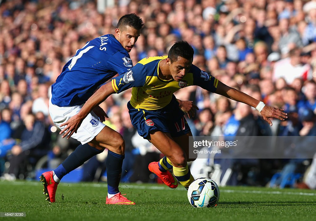 Alexis Sanchez of Arsenal competes with Kevin Mirallas of Everton during the Barclays Premier League match between Everton and Arsenal at Goodison Park on August 23, 2014 in Liverpool, England.