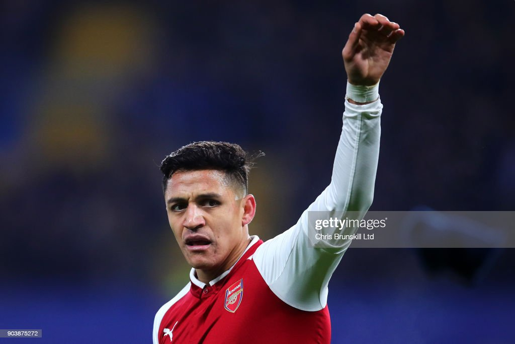 Alexis Sanchez of Arsenal discards his glove during the Carabao Cup Semi-Final first leg match between Chelsea and Arsenal at Stamford Bridge on January 10, 2018 in London, England.