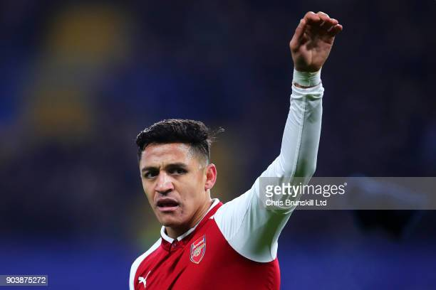 Alexis Sanchez of Arsenal discards his glove during the Carabao Cup SemiFinal first leg match between Chelsea and Arsenal at Stamford Bridge on...