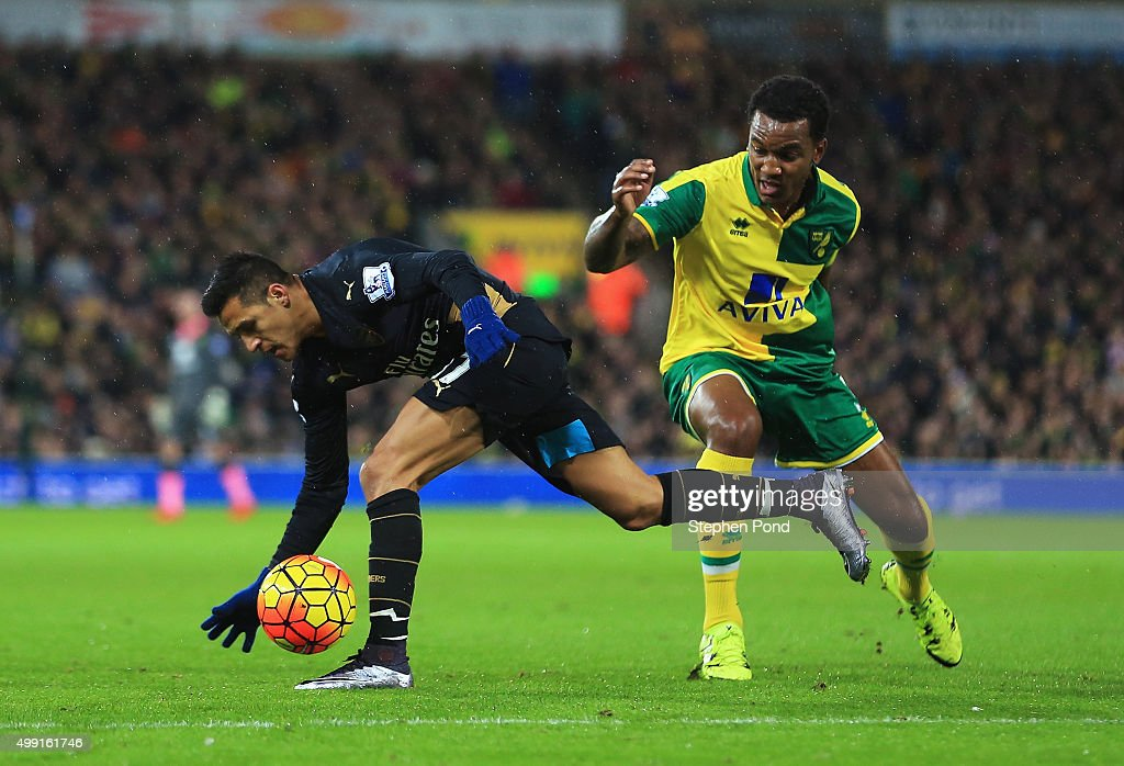 Alexis Sanchez of Arsenal evades Andre Wisdom of Norwich City during the Barclays Premier League match between Norwich City and Arsenal at Carrow Road on November 29, 2015 in Norwich, England.
