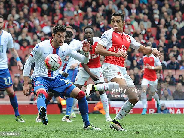 Alexis Sanchez of Arsenal flicks the ball passed Joel Ward of Palace during the Barclays Premier League match between Arsenal and Crystal Palace at...