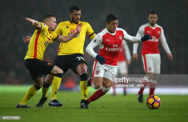 Alexis Sanchez of Arsenal gets past Tom Cleverley and Etienne Capoue of Watford during the Premier League match between Arsenal and Watford at...