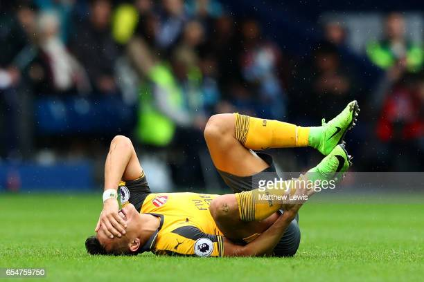 Alexis Sanchez of Arsenal goes down in pain during the Premier League match between West Bromwich Albion and Arsenal at The Hawthorns on March 18...