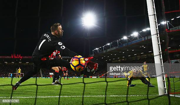 Alexis Sanchez of Arsenal heads to score his side's first goal past Artur Boruc of AFC Bournemouth during the Premier League match between AFC...